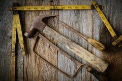 Martelo, serra, chave de fenda e fita de medição Foto de Stock