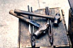 Martelos velhos e tenazes de brasa do ferreiro para trabalhar o aço imagens de stock