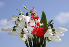 Martenitsa on background of blue sky and snowdrop stock image