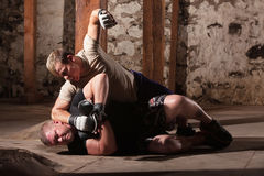 Martial Artist Punching Man on Ground Stock Photo