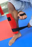 Martial artist putting on leg guard stock photography