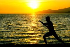 Martial arts. Silhouette of man practicing martial arts on a beacha at sunset Stock Photography