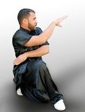 Martial Arts. Man sitting in a martial arts Stance Royalty Free Stock Photography