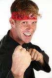 Martial Arts. Attractive 30 something man in martial arts uniform punching towards camera Stock Photo
