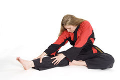 Martial Arts. Female martial artist in red and black uniform stretching stock image