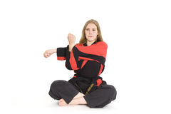 Martial Arts. Female martial artist in red and black uniform stretching royalty free stock image