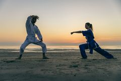 Martial arts athletes. Two martial arts athletes training  on the beach at sunrise - Sportive men and women ready to fight - Kung fu and karate masters Stock Image