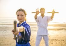 Martial arts athletes. Two martial arts athletes training with weapons on the beach at sunrise - Sportive men and women with stick and nunchaku - Kung fu and Royalty Free Stock Image