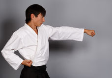 Martial arts attack. Man on grey background standing in fighting pose ready to attack Stock Photography
