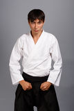 Martial arts. Bellicose man on grey background standing in fighting pose Stock Photography