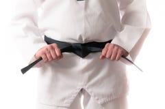 Martial Arts Black Belt. Man in martial arts uniform holding his black belt with both hands Stock Images