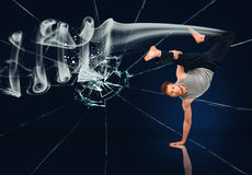 Martial arts expert doing hand stand against broken glass background. Martial arts expert doing hand stand with smoke trailing him against broken glass Stock Photography