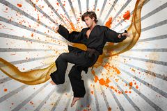 Martial arts expert mid air. On linear pattern with orange paint splashes and vapour Royalty Free Stock Photography