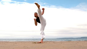 Martial arts expert practicing on the beach stock video