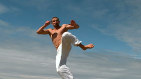 Martial arts expert practicing by the coast stock footage