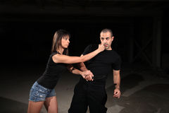 Martial arts female instructor. Exercising with young man stock image