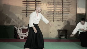 Martial arts Master in black hakama. Two athletes in a kimono demonstrating martial arts techniques. martial arts stock footage