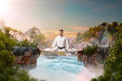 Martial arts master in kimonodo sitting on splits. Martial arts master in white kimonodo sitting on the splits, stretching exercise over beautiful lake Royalty Free Stock Photo
