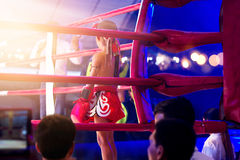 Martial arts of Muay Thai boxer kid with items in boxing ring coner. Martial arts of Muay Thai boxer kid with items in boxing ring corner among floodlights and Stock Photography