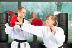 Martial Arts sport training in gym. People in a gym in martial arts training exercising Taekwondo, both have a black belt Stock Photos