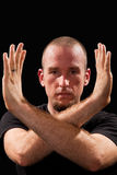 Martial arts teacher posing. A martial arts teacher poses with his arms framing his face Royalty Free Stock Photography