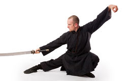 Martial arts teacher with sword out. A martial arts teacher poses in a seated stance with a sword pointed out Stock Photos
