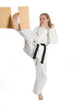 Martial Arts Woman. Third degree black belt braking a board with a front kick royalty free stock photography