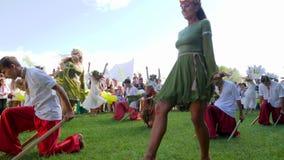 Martial dansenjongens op aard, nationale dansen, meisjes het dansen volksdansen in kostuums in de open lucht op slavic vakantieiv stock video