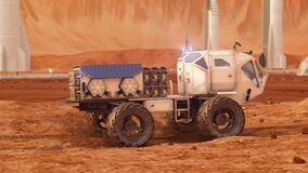 The Martian rover is moving on the surface of Mars. The base of the colonists in the background. 4k footage