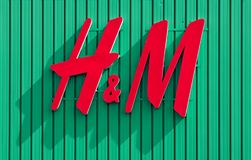 H&M logo on green background of the store located in Fiera mall. It is a multinational clothing retail company. stock image