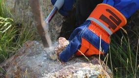 Martilleo con un martillo de los geólogos en piedra almacen de metraje de vídeo