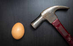 Martilleo de un huevo en la tabla negra Fotos de archivo
