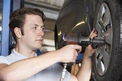 Martillo de aire de In Garage Using del mecánico en la rueda de coche Fotografía de archivo