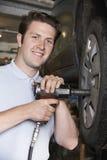 Martillo de aire de In Garage Using del mecánico en la rueda de coche Fotografía de archivo libre de regalías
