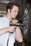 Martillo de aire de In Garage Using del mecánico en la rueda de coche Imagenes de archivo