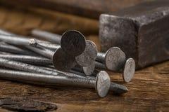Martillo de la vendimia con los clavos en el fondo de madera Imagen de archivo