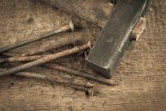 Martillo de la vendimia con los clavos en el fondo de madera Fotos de archivo