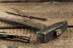 Martillo de la vendimia con los clavos en el fondo de madera Foto de archivo libre de regalías
