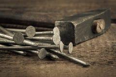 Martillo de la vendimia con los clavos en el fondo de madera Imágenes de archivo libres de regalías