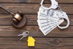 Martillo del juez, billetes de dólar, esposas, llaves con un llavero bajo la forma de casa Foto de archivo