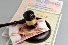 Martillo del juez con las partidas del dinero, maternales y de nacimiento en g Foto de archivo libre de regalías