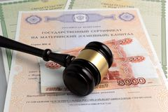 Martillo del juez con las partidas del dinero, maternales y de nacimiento en g Fotos de archivo libres de regalías