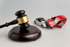 Martillo del juez con los modelos del accidente de tráfico en gris Imágenes de archivo libres de regalías