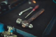 Martillo, destornillador y llave en fondo negro fotos de archivo