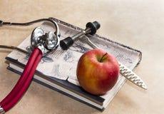 Martillo neurológico, libro médico y manzana roja imagen de archivo libre de regalías