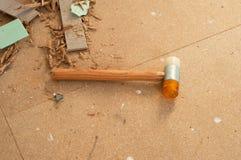 Martillo para la instalación laminada y restos de las rebanadas laminadas en el piso imagen de archivo libre de regalías