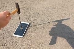 Martillo que rompe la pantalla de un smartphone Imágenes de archivo libres de regalías
