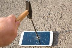 Martillo que rompe la pantalla de un smartphone Imagen de archivo