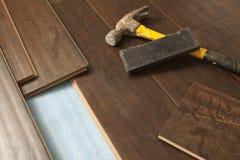 Martillo y bloque con el nuevo suelo laminado Fotos de archivo libres de regalías