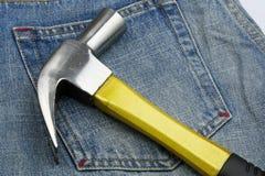 Martillo y pantalones vaqueros foto de archivo libre de regalías